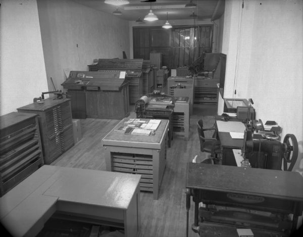 Wells Printing Company's new plant interior. Many pieces of letterpress equipment can be seen; type cabinets, a composing stone with set type on it and a proof press.