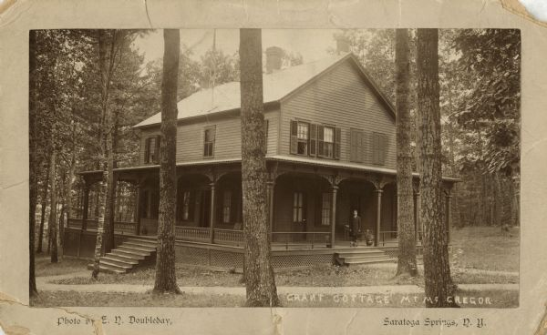 Exterior view of Grant Cottage with man and dog standing on the porch.