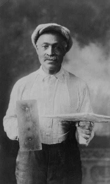 Portrait of Henry Mathews, 1866-1941, an early African American resident, holding the tools of his trade in front of a painted backdrop. He was a stone mason for many years.