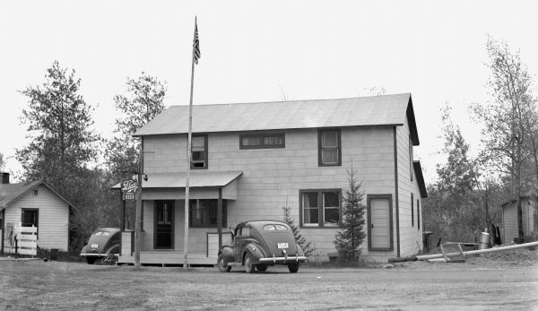 Two automobiles are parked next to a tavern with a Blatz Beer sign hanging out front. An American flag hangs from a flagpole.