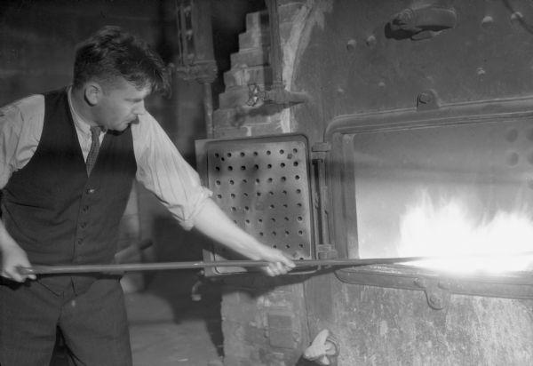 Man Stoking Furnace | Photograph | Wisconsin Historical Society