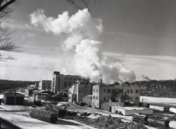Smoke billowing from smokestacks at the Consolidated Paper plant. The river appears to be partially frozen, and snow is on the ground. Piles of logs, on the ground and in open railroad cars, are in the foreground.