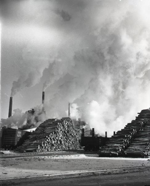 View across railroad tracks of billowing smokestacks at the Thilmany Paper Company plant. Stacks of logs are piled next to railroad tracks and cars.