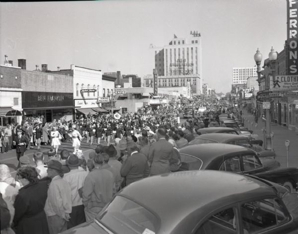 Street view of a parade on College Avenue at Walnut Street. Crowds and cars line both sides of the street, looking on as bands, cars, and floats pass by. Local businesses are also visible, including a Ben Franklin store.