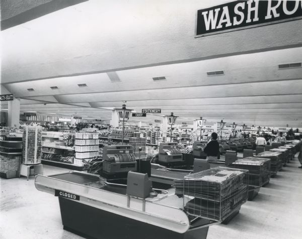 Interior of the Treasure Island Store, located on West College Avenue. Store aisles and end-caps full of goods are visible. A single cashier waits in aisle 8 while other cashiers assist customers in the background. Each check-out counter has a stack of newspapers at the end. The Treasure Island was the first discount box store in the Fox River Valley.