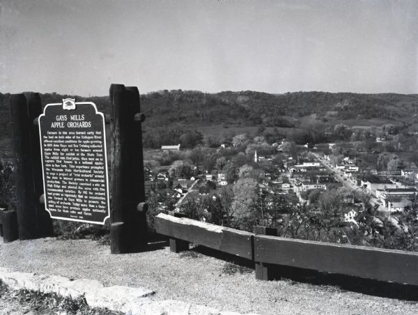 Image of the historical marker for Gays Mills Apple Orchards overlooking the town of Gays Mills, Wisconsin. The marker stands to the left, leaving an elevated view of the town's business and residential areas. Cars are lining the street along one of the main roads.