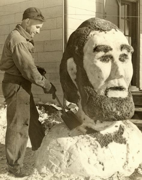 A man uses a shovel to carve out a large bust of Abe Lincoln out of snow.