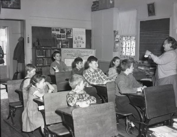 Class of young boys and girls in a one-room school house. The children sit in three rows of school desks, watching their teacher as she instructs. Books and educational literature are visible in the background.