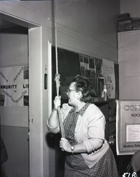 Teacher pulling on a rope to ring the school bell in a one-room school house. School literature and a chalkboard are visible in the background.