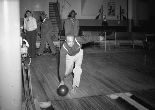 Down-lane view of Isaiah Pyant, member of C.I.O., bowling. A few men are visible in the background walking past, looking on and sitting on a bench.