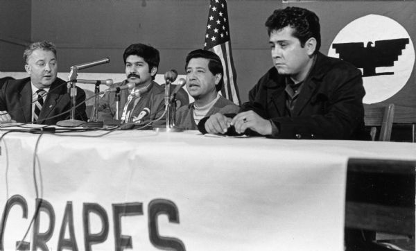 "John Schmitt, AFL CIO president; Manuel Salas, labor contractor for Libby, McNeil and Libby; Cesar Chavez and Eliseo Medina sit together on a panel in Milwaukee speaking about the grape boycott. The table has numerous microphones and has a banner hanging on it that reads in part ""Grapes."" An American flag and an Farm Workers AFL-CIO flag are hanging in the background. <p></p>Panel del boicot de uvas en Milwaukee <p></p>John Schmitt, presidente de AFL CIO; Manuel Salas, contratante laboral para Libby, McNeil & Libby; Cesar Chávez y Eliseo Medina sentados durante un panel en Milwaukee para hablar acerca del boicot de uva. La mesas tienen micrófonos numerosos y un estandarte colgando que en parte se lee la palabra ""Uvas"" (""Grapes""). Una bandera americana y una bandera de Farm Workers AFL-CIO se pueden ver colgando en el fondo."