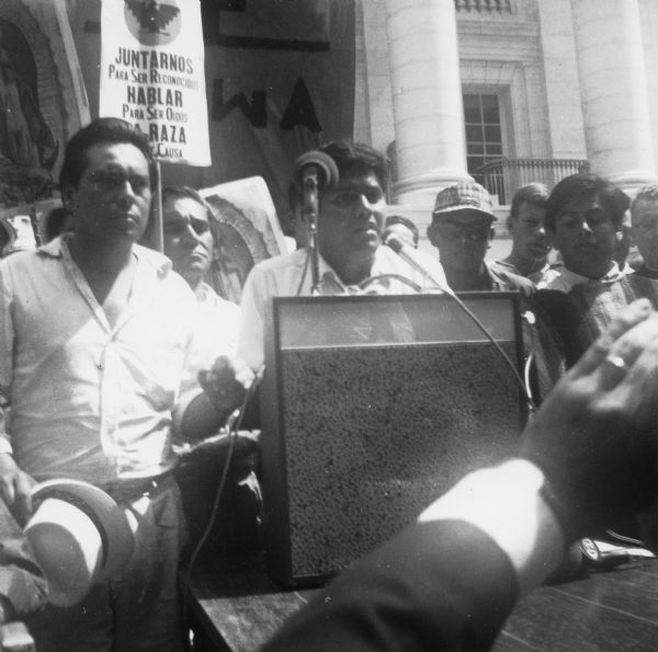 "Jesus Salas addresses a rally at a podium in front of the Wisconsin State Capitol. Behind him are marchers who began the march from Wautoma and walked to Madison on Highway 21. Marchers are holding images of Our Lady of Guadalupe, a National Farm Worker Association's banner, and signs with the message ""Juntarnos para ser reconocidos. Hablar para ser oidos. La raza tiene causa""/ ""Join us to recognized. Speak to be heard. The people have a cause.""    This photograph is a part of Wisconsin-native David Giffey's series ""Struggle for Justice,"" images from the migrant farm worker struggle including an independent oganizing effort in Wisconsin and the nationwide grape boycott movement started by Cesar Chavez of United Farm Workers during the 1960s and 1970s. <p></p>Salas se dirige al público <p></p>Jesús Salas le habla al público desde un podio enfrente del Capitolio del estado de Wisconsin. Detrás de él están unos manifestantes que marcharon desde Wautoma y caminaron hacia Madison en la carretera Highway 21. Unos manifestantes están sosteniendo imágenes de Nuestra Señora de Guadalupe, el estandarte de National Farm Workers Association (NFWA), y letreros que dicen, ""Juntarnos para ser reconocidos. Hablar para ser oídos. La raza tiene causa."" Esta fotografía es parte de la serie ""Lucha por la Justicia"" tomada por David Giffey, originario de Wisconsin, las imágenes muestran la lucha de los trabajadores agrícolas emigrantes incluyendo un esfuerzo independiente organizado en Wisconsin y el movimiento nacional del boicot de uvas empezado por Cesar Chávez de la unión de campesinos o United Farm Workers durante los años 1960 y 1970."