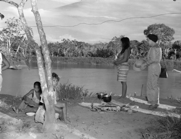 Indigenous Panamanian women and children eating dinner along the Chucunaque River. A woman in a jumpsuit holding a hat watches Panamanian children eating. A Panamanian woman stands by two pots and food and the remains of a fire. Behind them is the Chucunaque River and trees.