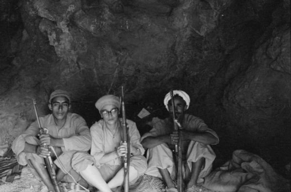 Photographer Dickey Chapelle sits with Algerian members of the National Liberation Front dressed as a member of the FLN. She is wearing a head scarf and holding a rifle while seated in a cave.