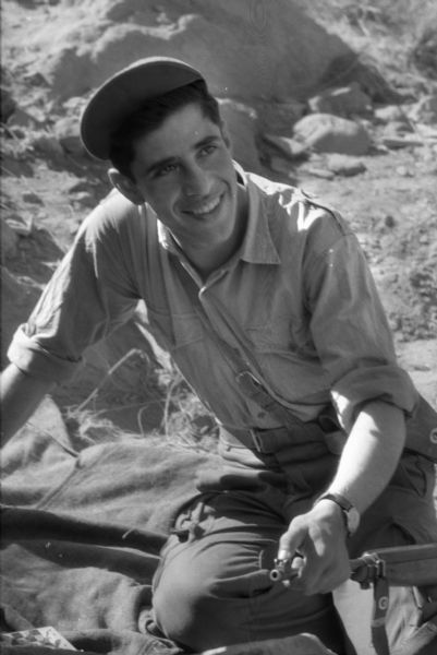 A young Algerian member of the National Liberation Front smiles and poses for a photograph with his gun.