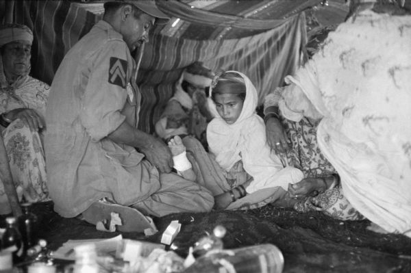 A young Algerian girl has her foot treated by a Red Crescent (Red Cross equivalent) worker in a tent. The man is wrapping the girl's foot in bandages. She is wearing a cloak and a patterned dress. Beside her are two women and behind her is another woman with a baby. There are medicine bottles in the foreground.