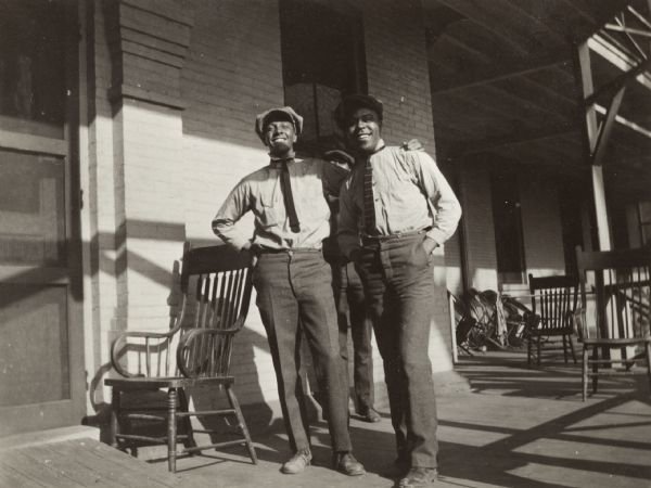 Snapshot of two African American men standing on a porch by a wooden chair in front of a brick building. A third man is standing behind them. The men are wearing hats, button-up shirts and ties.