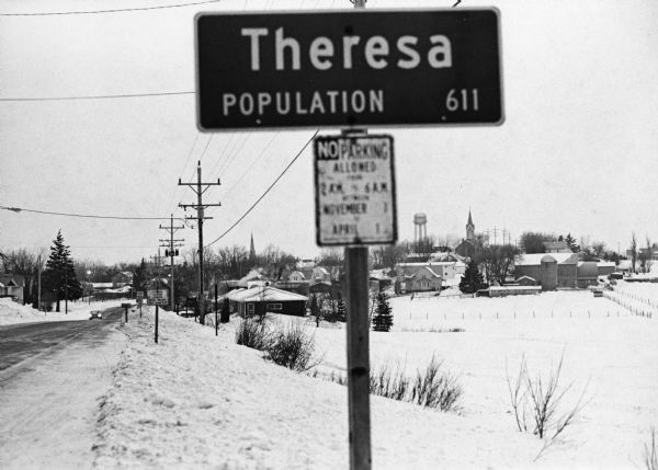 """In the early morning hours, a new month dawns on the small village of Theresa.  The village is now in the 130th year of its existence.""  The village marker reads, ""Theresa, Population 611."""