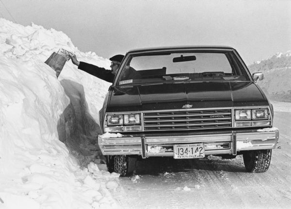 "Winter scene with mail carrier in car putting mail in a mailbox.  ""Ralph Koll, Rural Mail Carrier. Somewhere in this monstrous snow drift is Helen Moldenhauer's mail box. Ralph Delivers to 264 boxes on his 63.6 mile route. In eighteen winters of mail delivery, Ralph reports that this winter was the most severe."""