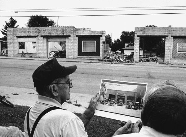 """Les Beck displays a 1930s photograph of the garage that is being displaced by the present-day Theresa Cwik Mart."""