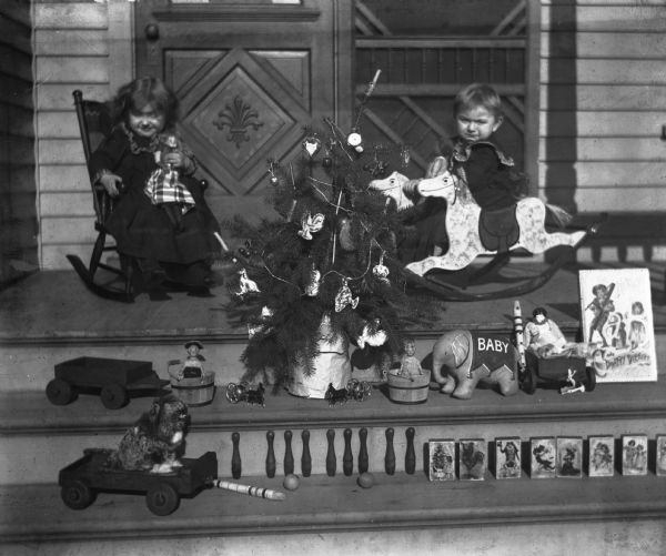 Jennie, in rocking chair, and Edgar Krueger, on a rocking horse, with small Christmas tree and toys, including wagon, blocks, and doll, displayed outside on the steps of the porch.