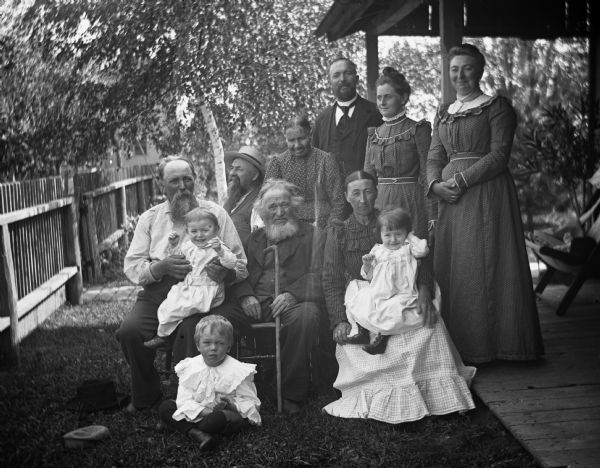 Charles Goetsch and Krueger family. Rexford Krueger (on lawn), August Krueger, Edgar (on lap), with William Krueger, (holding cane), Charles Goetsch (looking up), Mrs. Charles Amelia Goetsch, Henry Krueger, Mary Krueger holding Jennie, Mrs. Alex Krueger and Sarah Krueger Bhend.