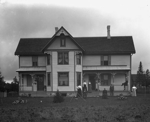 Exterior view of the William Wills homestead. The family, including a dog, is standing around the front porch. One young girl is standing inside the house looking out of the large window on the porch.