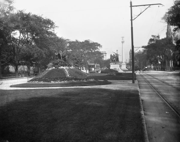View down Grand Avenue. Near a streetcar is the city's Civil War memorial, erected in 1898 by John Conway.