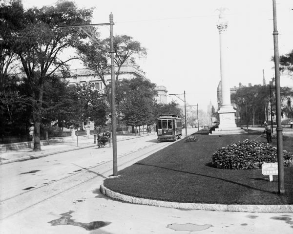 View down Grand Avenue. A streetcar and a horse-drawn wagon are coming up the avenue. There are monuments in the median.