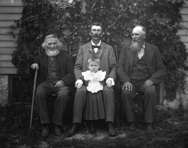 Outdoor group portrait of four generations of three Krueger men and one boy. Sitting left to right are: William (holding cane), Alexander and August Krueger. Edgar Krueger is standing in the middle, between his father's legs.