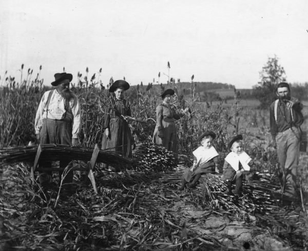 August, Tina, Sarah, Jennie, Edgar and Alex Krueger posing outdoors in a field. Alex took this photograph remotely with a string tied to the shutter of the camera. They are all wearing hats except Alex, and the two young children have large collars over their clothing.