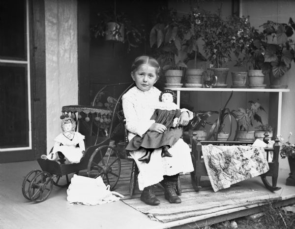 Young Jennie Krueger, the photographer's daughter, sitting with her dolls on the porch.