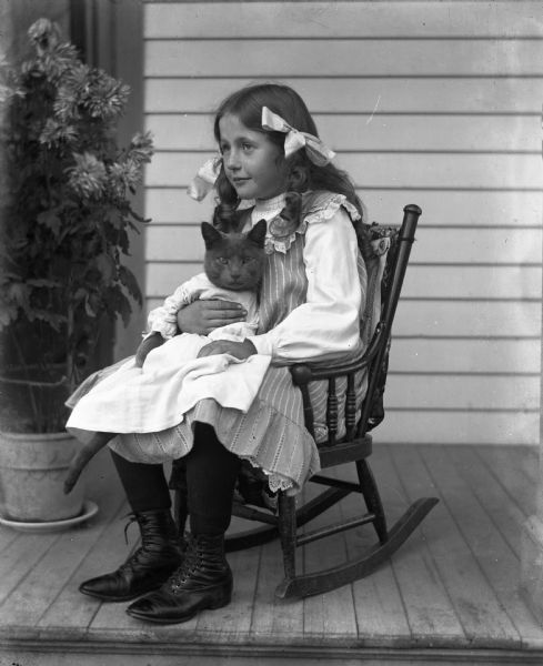 Jennie Krueger sitting in a rocking chair on a porch holding her cat Tramp, who is dressed in baby clothes.
