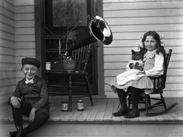 "Edgar and Jennie Krueger are sitting on the front porch of the Krueger home with an Edison Standard phonograph sitting on a chair between them. Two Edison Gold Moulded Records cylinders are under the chair. Jennie is holding their cat named ""Tramp"" on her lap. The cat is wearing a dress."