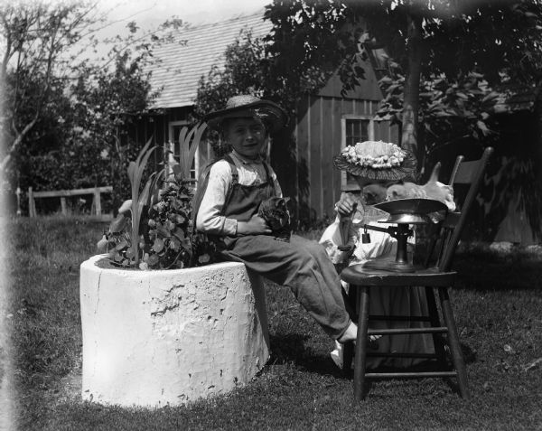 Edgar and Jennie Krueger outdoors in the yard. Edgar is sitting on a concrete planter holding a kitten in his lap. Jennie is kneeling in the grass weighing kittens on a scale set up on a chair.