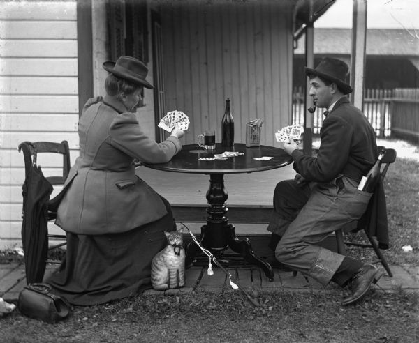 Sarah Krueger and Henry Bigalk playing cards at a table set up outdoors next to the porch. Henry is smoking a pipe and has a large bottle of alcohol sticking out of the back pocket of his overalls, which he has on over his suit pants. On the table is a bottle, a mug, and a bag of tobacco. A stuffed animal cat is leaned up against the side of Sarah's dress, and August Kruger's long pipe is resting on the bottom leg of the table.