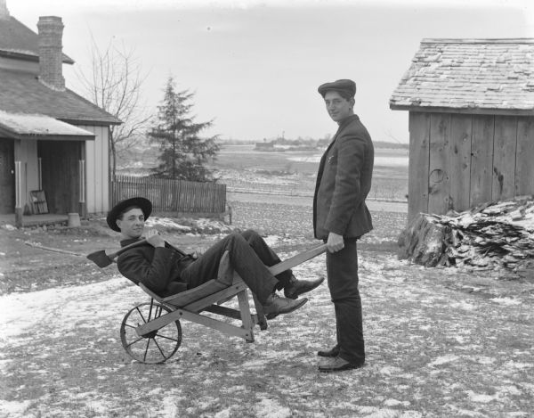 Henry Bigalk relaxes in a wheelbarrow holding an axe in his left hand, while Emil Kuney (Keune) is grabbing the wheelbarrow handles as if to transport Bigalk away. Behind them is an outbuilding on the right, and a house is on the left. In the far distance across a field are more buildings. Snow is on the ground.