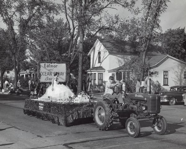 Parade float sponsored by Eatmor and Ocean Spray Cranberries. A beauty queen sits on the float surrounded by cranberry products. The float is being pulled by an International Harvester Farmall A tractor.