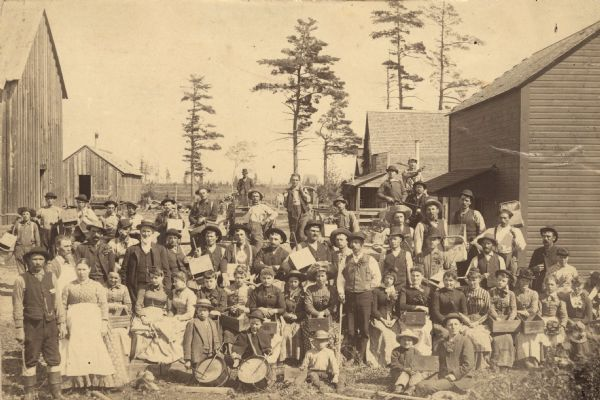 Large group of cranberry harvesters posing with implements. Many of the individuals are wearing boutonnières and corsages made from cranberry sprigs. Many of the implements have the initials C&S printed on them.