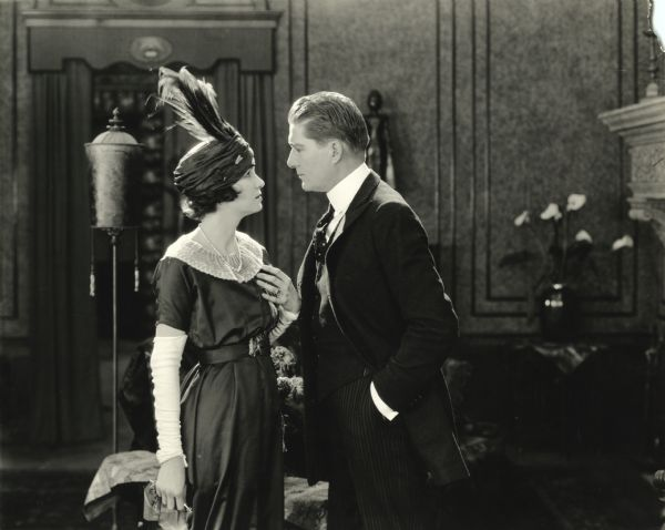 "Justine Spotiswood (played by Irene Castle wearing a turban with feathers) and Cosmo Spotiswood (William P. Carleton) gaze into each others eyes in a scene still from the silent film ""The Amateur Wife"" (Lasky 1920)."