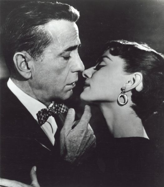 "Humphrey Bogart and Audrey Hepburn are about to kiss in a publicity still for ""Sabrina"" (Paramount 1954)."