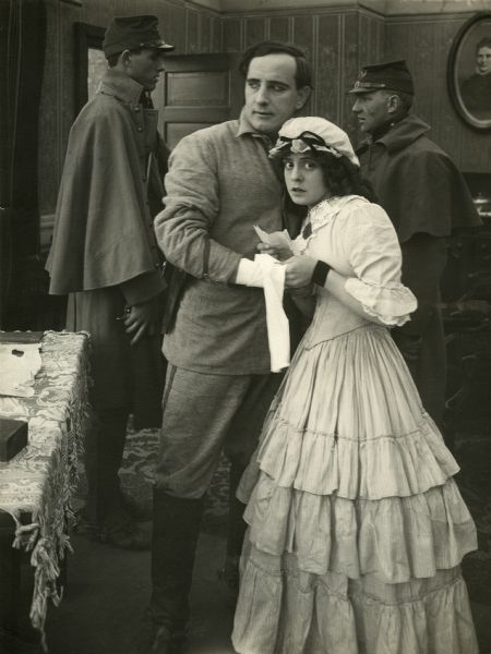 "William Clifford and Ethel Grandin in 1860s or 1870s period costume. They are apparently being guarded by two U.S. Army soldiers in this scene still for ""Across the Plains"" (Bison 1912)."