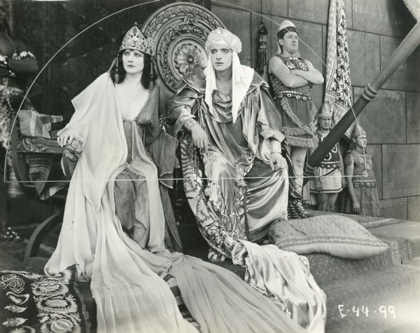 "Betty Blythe as the Queen of Sheba and Fritz Leiber as King Solomon in a still from ""The Queen of Sheba,"" a silent William Fox mega-production of 1921. They are seated on thrones with guards standing nearby."