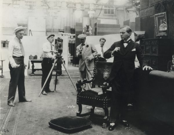 "Frederick A. Thomson (at left in straw hat), Charles J. Davis (cranking what appears to be a Moy & Bastie camera), J. Stuart Blackton (in cap and bow tie and wearing glasses), and the actor E. H. Sothern (far right) in a production still for a Vitagraph silent film, most likely ""The Chattel"" of 1916."