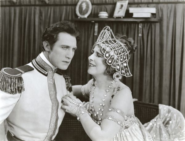 "Prince Michael Orbeliana (played by Lou Tellegen in an aristocratic white military uniform) visits the opera singer Marcia Warren (Geraldine Farrar wearing a pearl-covered headdress) in her dressing room in this scene still from ""The World and Its Woman."""