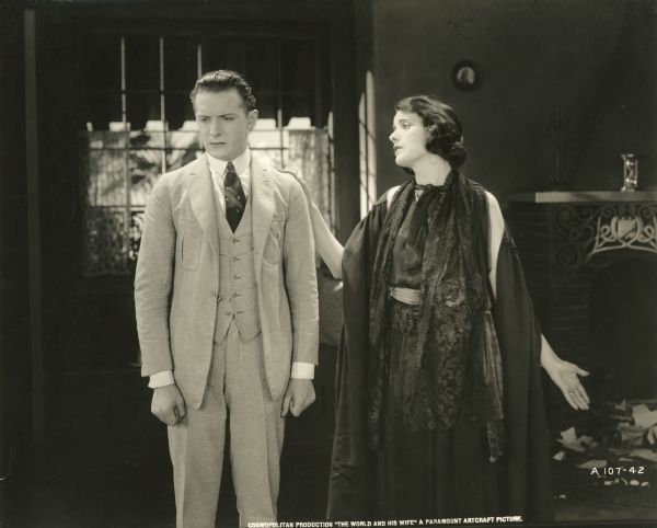 "Ernesto, in a light colored three-piece suit, and Teodora, in a black dress and several layers of wraps about her shoulders, have an earnest conversation in a scene still from ""The World and His Wife"" (1920). The actors are Gaston Glass and Alma Rubens."