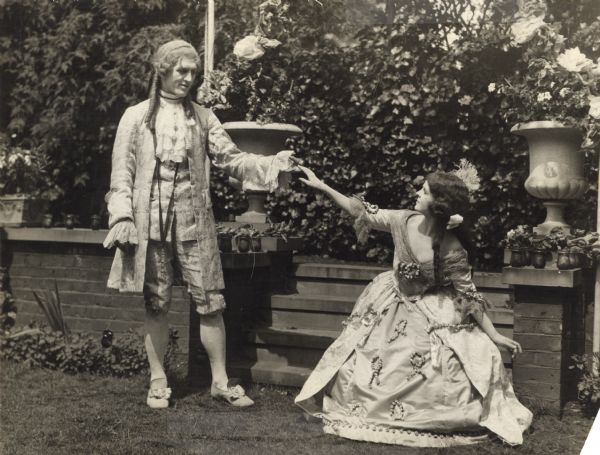 "Georges Carpentier lightly touches the hand of Flora le Breton who curtsies deeply in this scene still for ""A Gypsy Cavalier."" They are costumed in 18th century clothing: powdered wigs, ruffles, and lace."