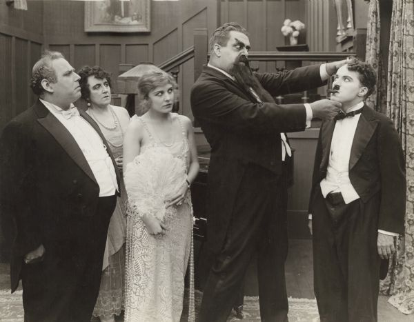 "In this scene still from Chaplin's 1917 silent film ""The Adventurer,"" Eric Campbell, made-up with large eyebrows, beard, and moustache, closely scrutinizes Charlie Chaplin's face. Watching, from left to right, are Henry Bergman, Marta Golden, and Edna Purviance."