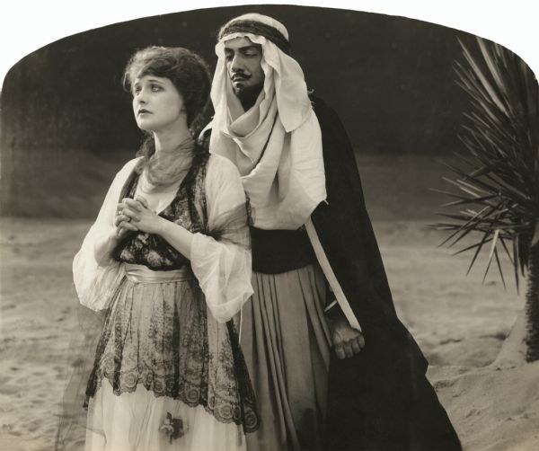 "English noblewoman Kathryn, Lady Wyverne (played by Elsie Ferguson), stands in a prayerful attitude in a scene still for the 1917 silent film ""Barbary Sheep."" She wears a white dress with a black lace coverlet. Looming close behind her is the Arab chieftan Benchaalal (played by Pedro de Cordoba). He wears a keffiyeh and dark robes and has a Van Dyke beard."