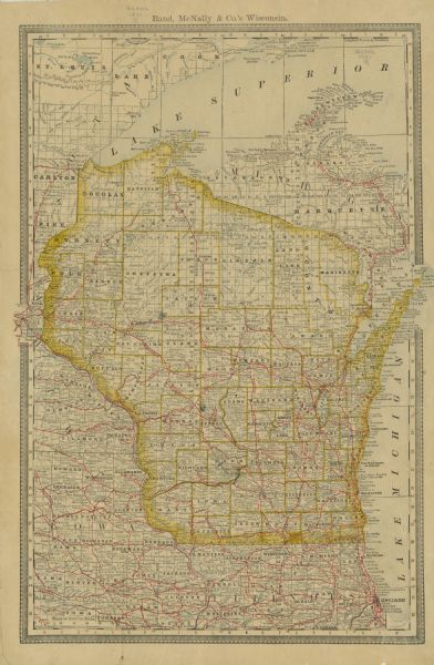 Map of Wisconsin including the eastern portions on Minnesota, Iowa, northern Illinois, and the western most portion of Michigan's Upper Peninsula, showing railroads, marked by red lines throughout these areas. The map also includes the locations of post offices, railroad stations, and lighthouses and harbors along the coasts of Lake Superior and Lake Michigan.